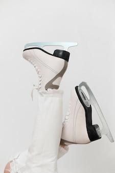 Vista lateral mujer vestida con patines de hielo blanco