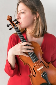 Vista lateral de la mujer en vestido posando mientras sostiene el violín