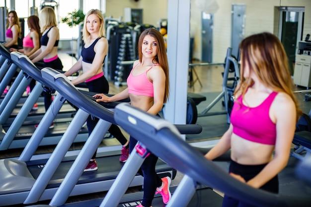 Vista lateral de las mujeres hermosas jovenes que se miran con sonrisa mientras que corre en la rueda de ardilla en el gimnasio