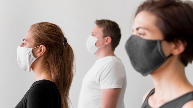Vista lateral de mujeres y hombres con máscaras