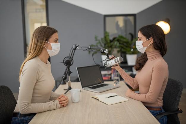 Vista lateral de mujeres con máscaras médicas transmitiendo juntas en radio