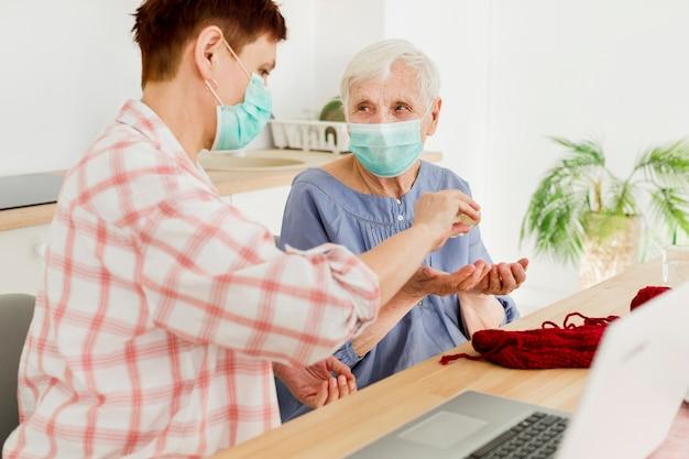 Vista lateral de las mujeres mayores en casa desinfectando sus manos