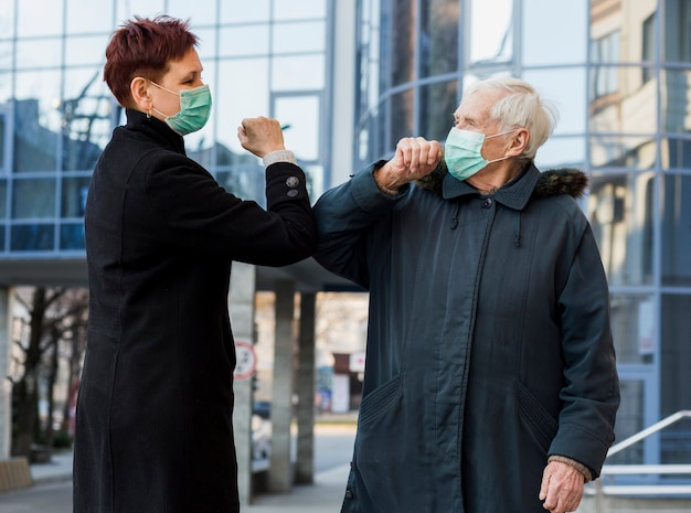 Vista lateral de las mujeres mayores golpeándose los codos mientras estaban en la ciudad como un saludo