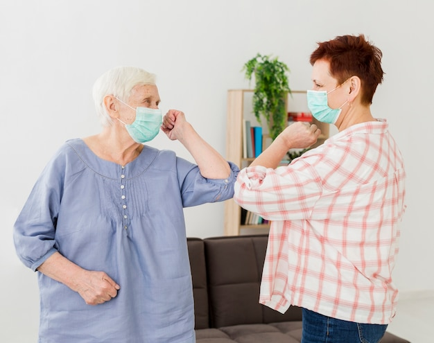 Vista lateral de las mujeres mayores que se saludan en casa