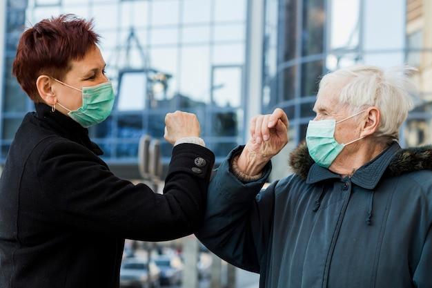 Vista lateral de mujeres mayores que usan codos para saludarse entre sí mientras usan máscaras médicas