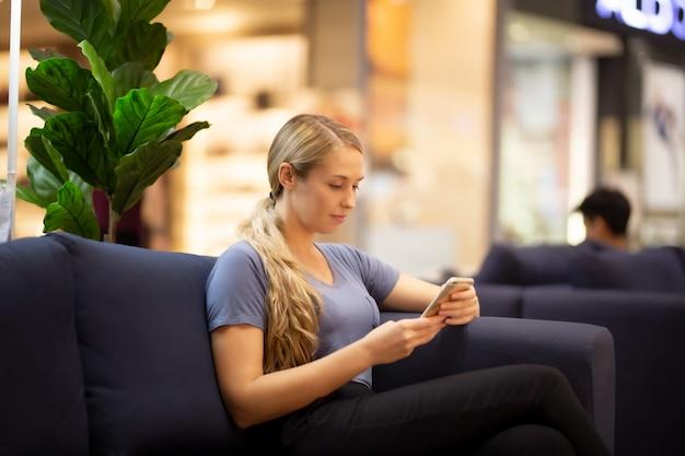 Vista lateral de las mujeres que buscan en el teléfono móvil con una sonrisa mientras está sentado en el sofá