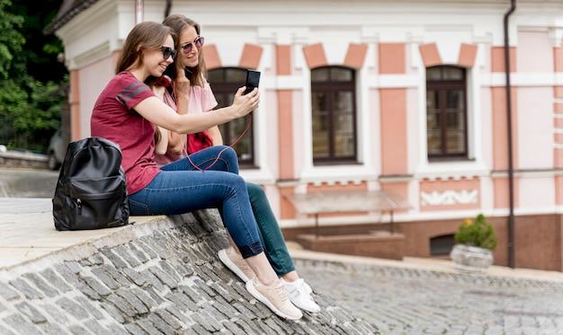 Vista lateral mujeres tomando selfie