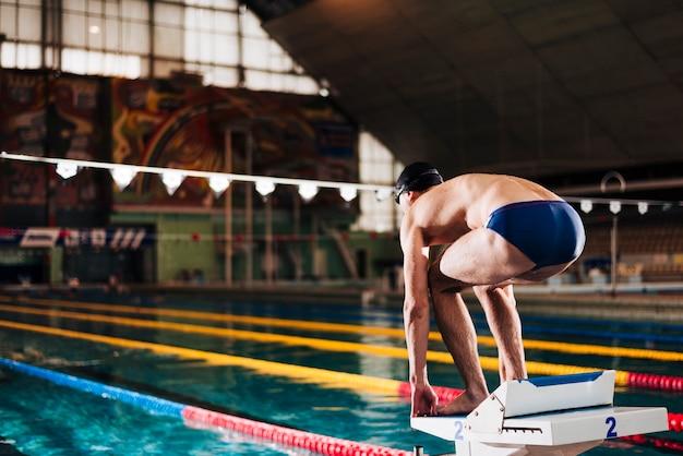 Vista lateral nadador masculino preparado para correr