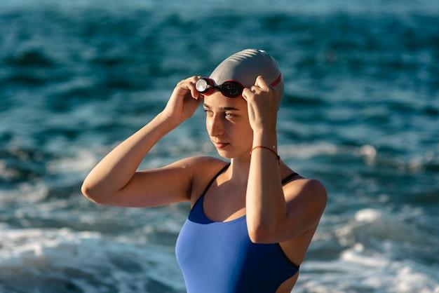Vista lateral de la nadadora con gorra y gafas de natación