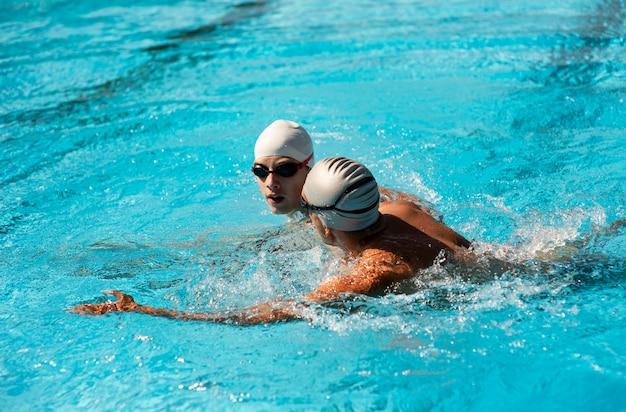 Vista lateral de nadadores masculinos nadando en la piscina