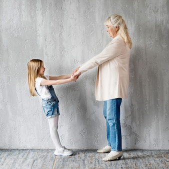 Vista lateral niña y abuela cogidos de la mano