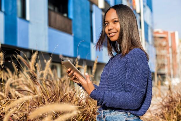 Vista lateral de una niña afroamericana de pie, mientras sostiene la tableta en sus manos y mira hacia otro lado