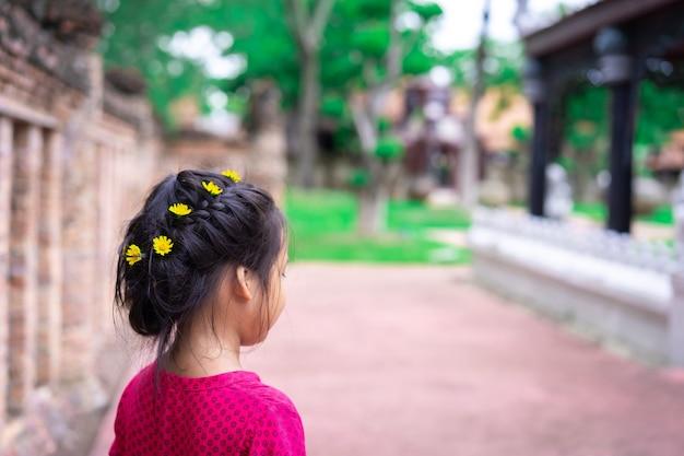 Vista lateral de la niña asiática en vestido rojo con un cabello hermoso y flor amarilla