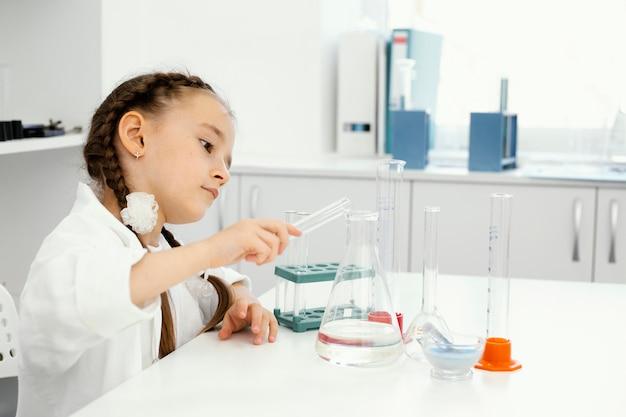 Vista lateral de la niña científica en el laboratorio con tubos de ensayo