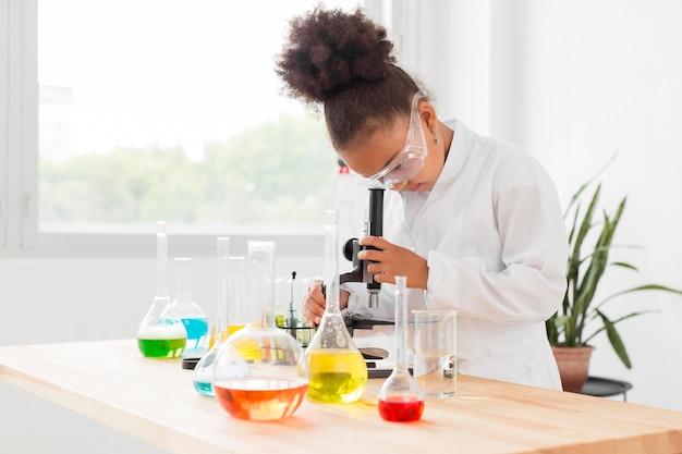 Vista lateral de la niña científico mirando a través del microscopio