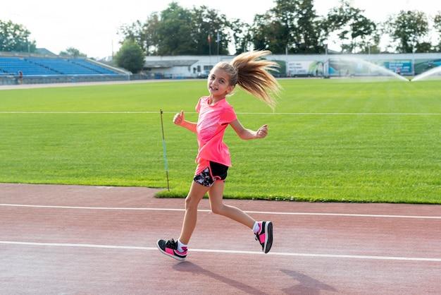 Vista lateral de la niña corriendo