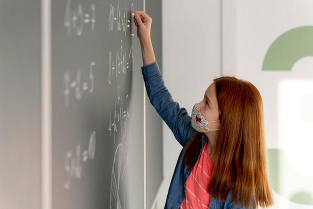 Vista lateral de la niña con escritura médica en la pizarra en clase