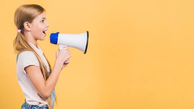 Vista lateral de una niña hablando en voz alta a través del megáfono contra el fondo amarillo