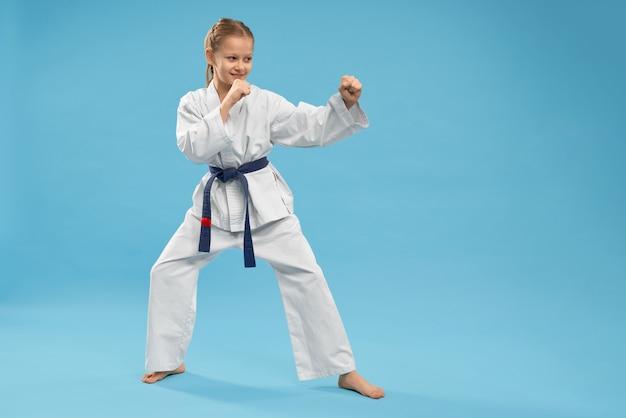 Vista lateral de la niña haciendo artes marciales sobre fondo aislado