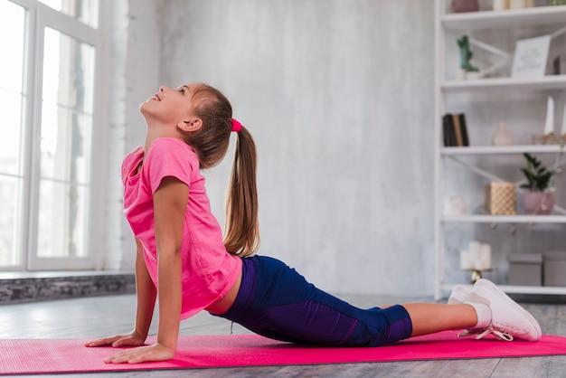 Vista lateral de una niña haciendo ejercicio en la colchoneta rosa