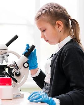 Vista lateral niña con microscopio