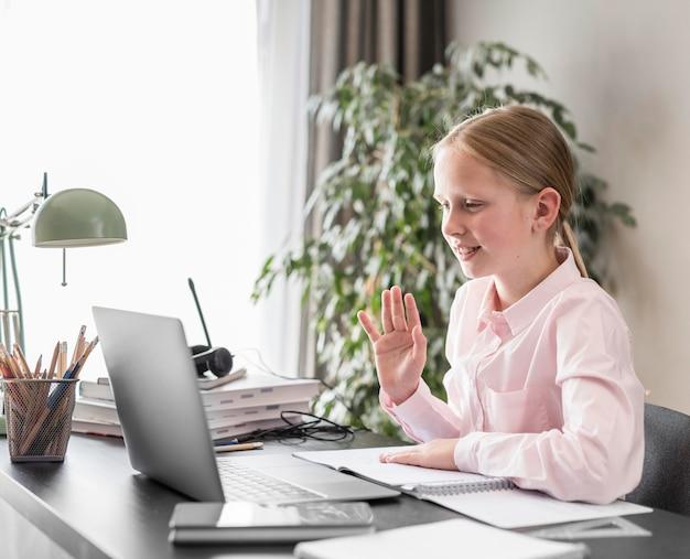 Vista lateral niña participando en clase en línea