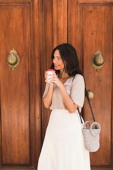 Vista lateral de una niña de pie delante de la puerta con una taza de café desechable