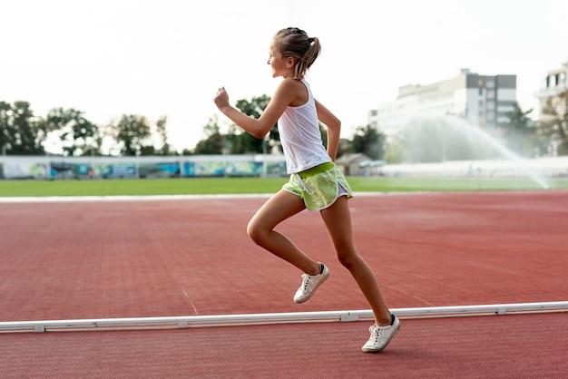 Vista lateral de la niña en la pista de atletismo