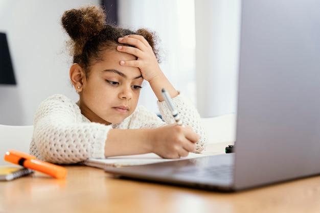 Vista lateral de la niña preocupada en casa durante la escuela en línea con portátil