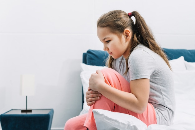 Vista lateral de una niña que tiene dolor en su rodilla sentada en la cama en su casa