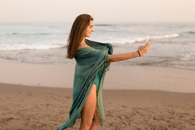Vista lateral de la niña que toma el autorretrato en el teléfono celular que se coloca en la playa