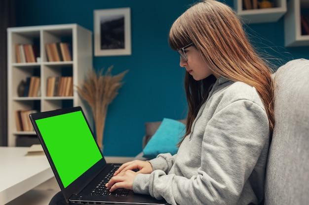 Vista lateral de la niña sentada en el sofá con la computadora portátil en el teclado de mecanografía de regazo, pantalla chromakey