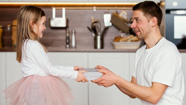 Vista lateral de la niña sonriente en falda tutú dando a su papá un regalo para el día del padre