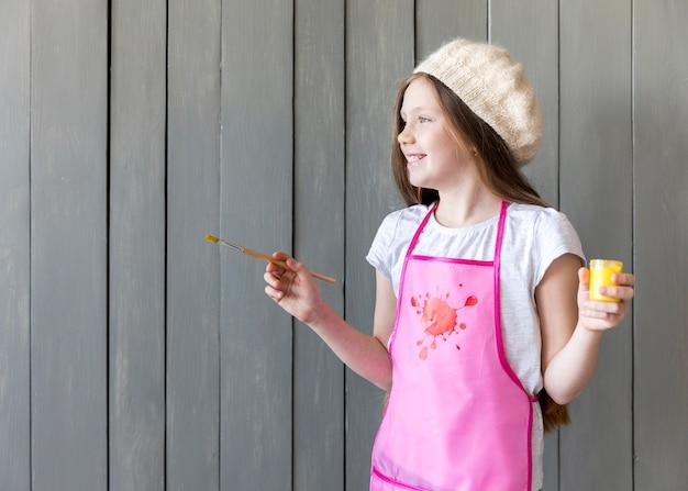 Vista lateral de una niña sonriente que sostiene una botella de pintura amarilla y un pincel en la mano de pie contra la pared de madera gris