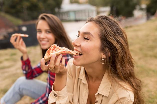 Vista lateral de las niñas sonrientes comiendo pizza