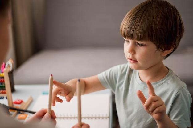 Vista lateral del niño aprendiendo a contar en casa usando lápices