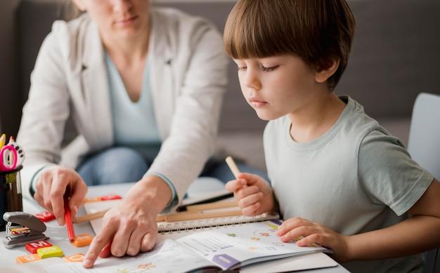 Vista lateral del niño aprendiendo del tutor en casa