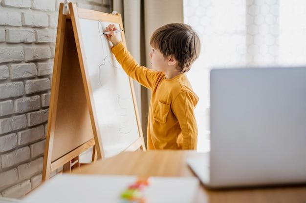 Vista lateral del niño en casa escribiendo en la pizarra mientras está en línea con tutoría