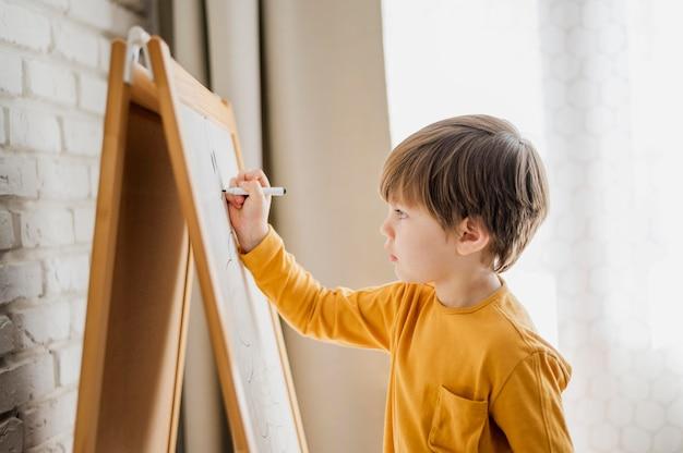 Vista lateral del niño en casa escribiendo en la pizarra