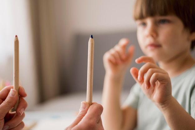 Vista lateral del niño desenfocado que recibe tutoría en casa