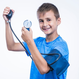 Vista lateral de un niño feliz que mide la presión arterial en el fondo blanco