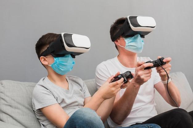 Vista lateral del niño y el hombre jugando con casco de realidad virtual mientras usan máscaras médicas