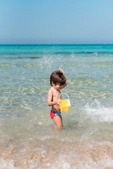 Vista lateral de un niño jugando con un balde en el agua en la playa
