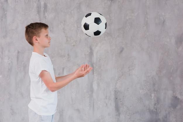 Vista lateral de un niño jugando con una pelota de fútbol contra un telón de fondo de concreto