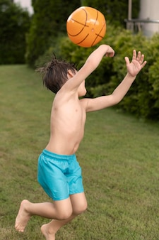 Vista lateral niño jugando con pelota