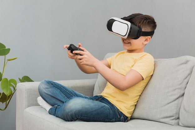 Vista lateral del niño jugando videojuegos con casco de realidad virtual