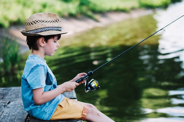 Vista lateral de un niño lindo de pesca en el lago