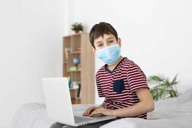 Vista lateral del niño con máscara médica posando mientras juega en la computadora portátil