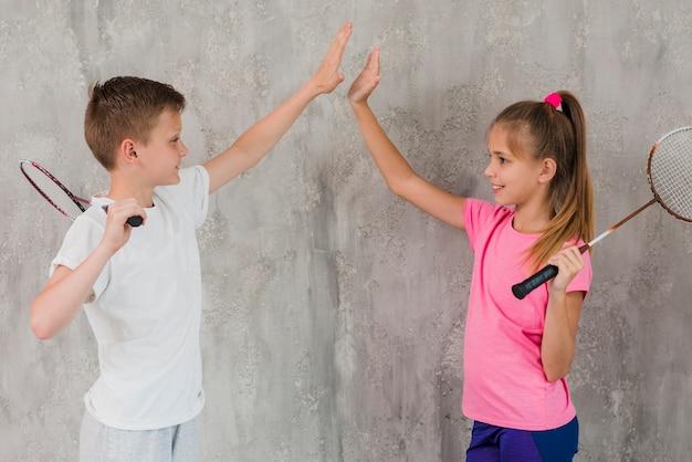 Vista lateral de un niño y una niña sosteniendo una raqueta en la mano dando cinco de pie contra la pared