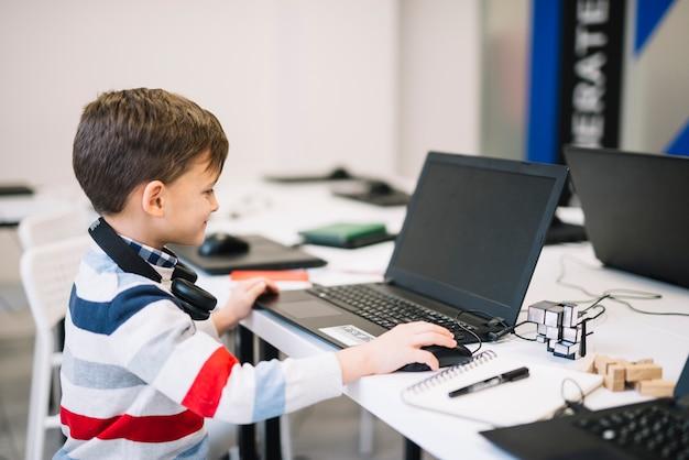 Vista lateral de un niño pequeño sonriente que usa la computadora portátil y el ratón en el aula